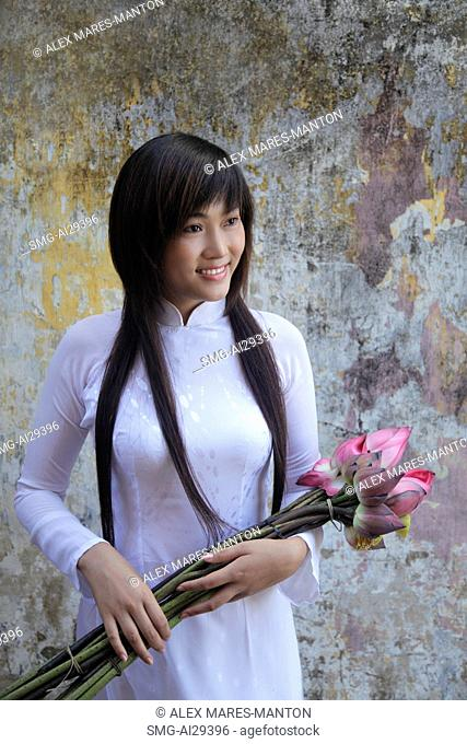 Young woman wearing traditional Vietnamese dress holding lotus flowers
