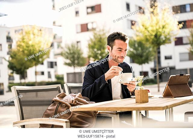 Businessman sitting in cafe, drinking coffee, using smartphone