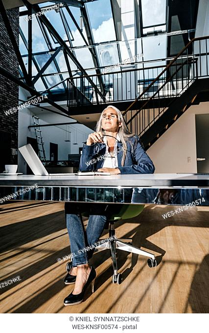 Businesswoman at desk enjoying sunlight
