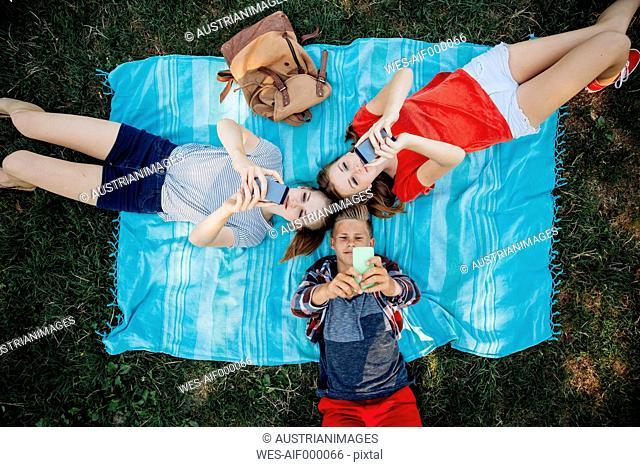 Three teenage friends with smartphones lying on blanket