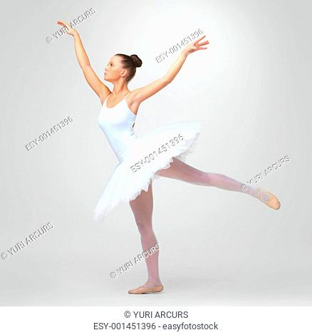 Full length of a young ballerina dancing gracefully against white background