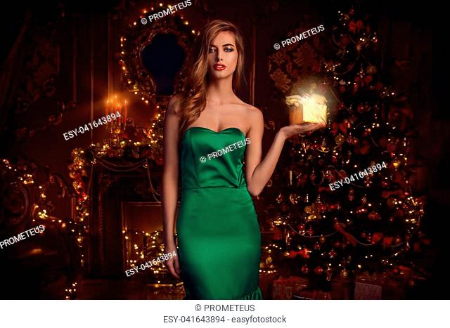 Magical Christmas night. Beautiful woman in evening dress with a gift box celebrates Christmas in luxurious apartments decorated christmas lights