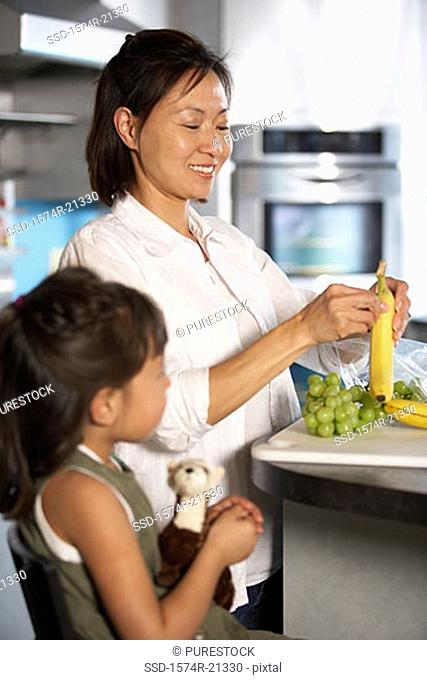 Mid adult woman peeling a banana with her daughter standing beside her in a kitchen