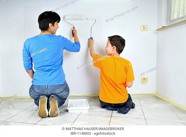 Paintwork, mother and son painting wall with paint rollers