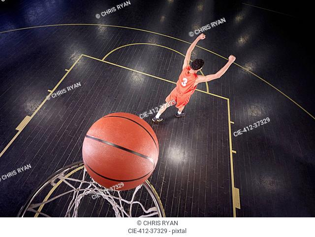 Confident young male basketball player shooting the ball and gesturing, celebrating