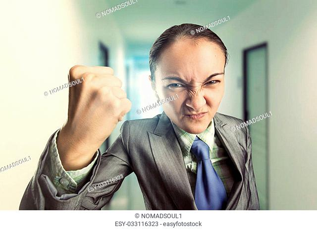 Angry irritated woman clenching her fist in the office