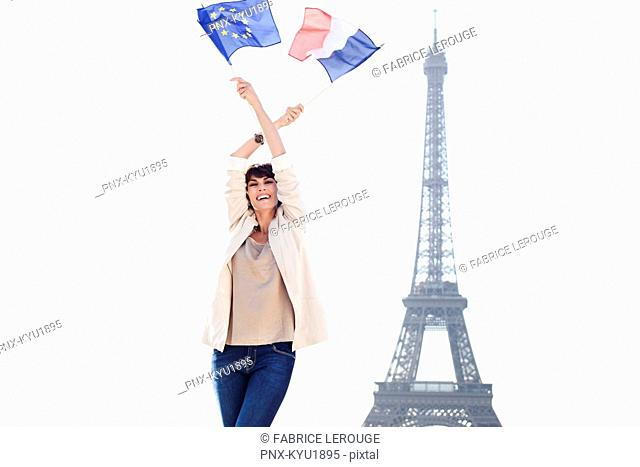 Woman holding a European Union flag and a French flag with the Eiffel Tower in the background, Paris, Ile-de-France, France