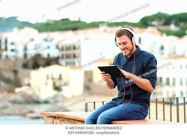 Happy man watching media on a tablet on a ledge with a town in the background