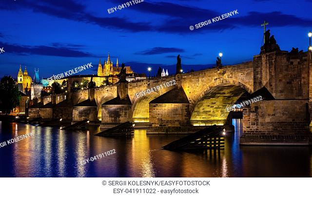 Illuminated Charles bridge at dusk in Prague