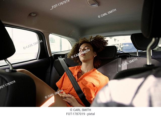 Tired young woman sleeping in back seat of car