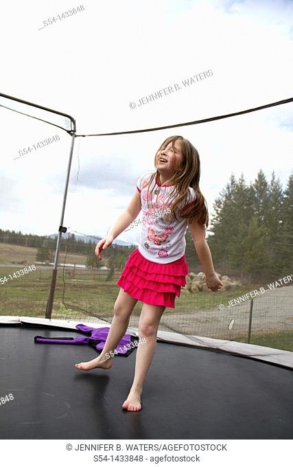 A girl, 5-10, jumping on a trampoline in Coeur d' Alene, Idaho, USA