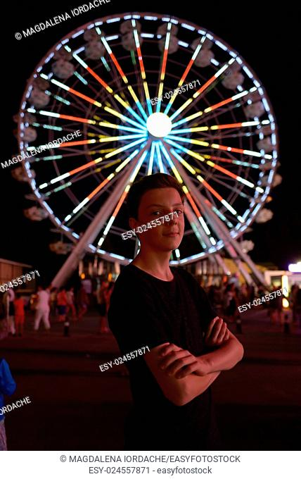 Teen boy in amusement park in night time