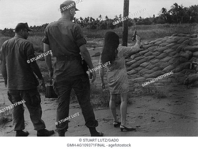 A pistol recoils and ejects a shell casing after a Vietnamese woman fires while two US Marines stand behind her and watch, during the Vietnam War, Vietnam, 1965