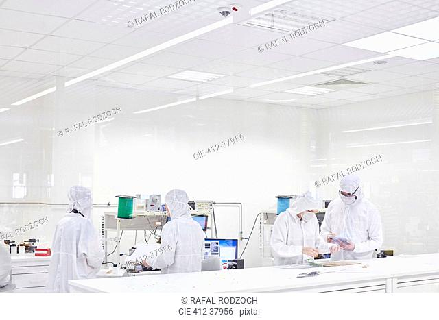 Engineers in clean suits using machinery in fiber optics research and testing lab