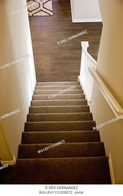 Stairs with handrail leading towards wooden floor at home; Moreno Valley; California; USA