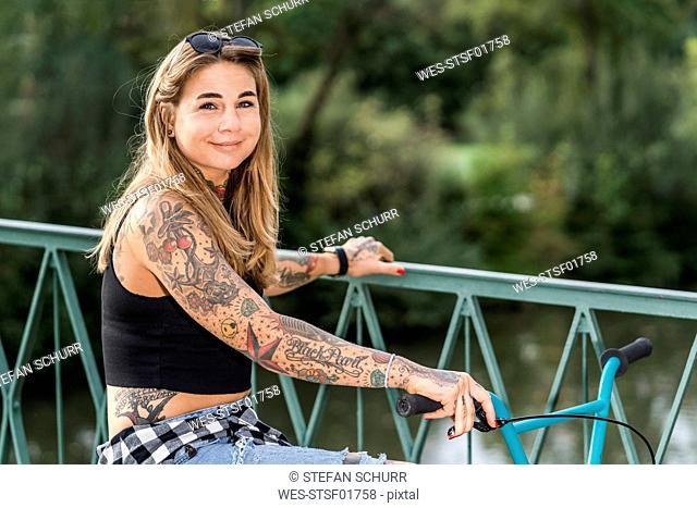 Portrait of a tattooed woman with a bike