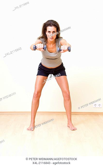 young woman exercising with barbells (model-released)