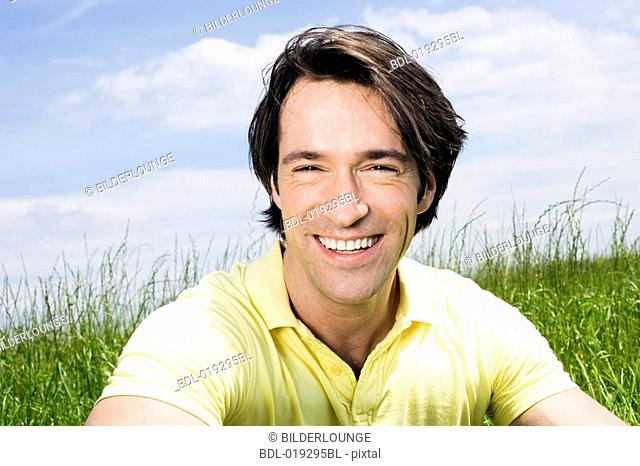 headshot of young man sitting in meadow