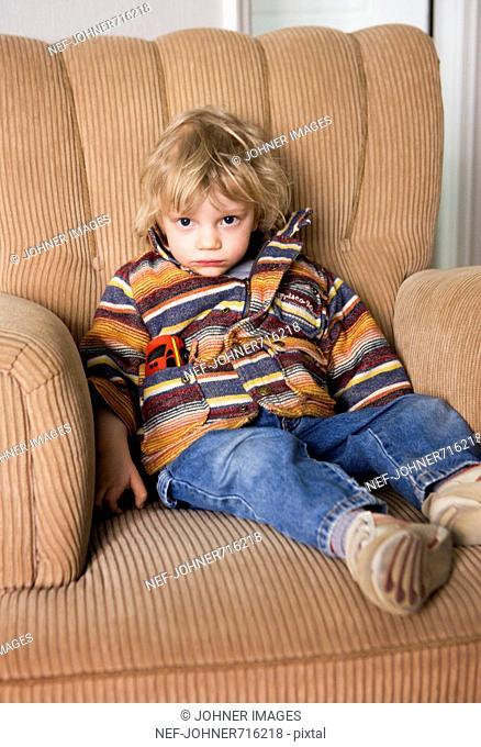 Sulky boy in an armchair, Sweden