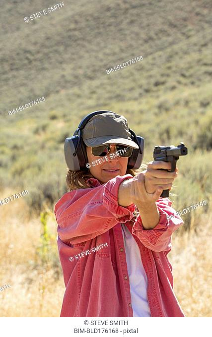 Caucasian woman aiming gun outdoors