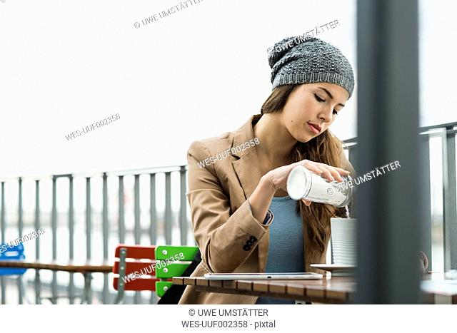 Young woman sitting at a sidewalk cafe