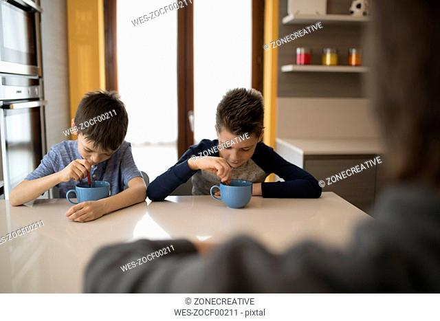 Two boys eating side by side at kitchen table