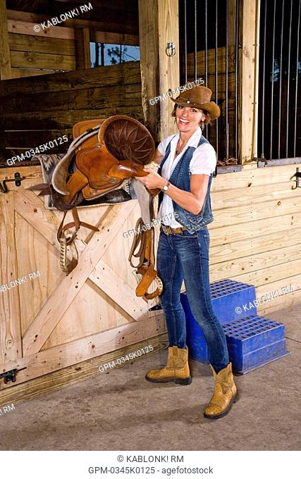 Attractive woman holding saddle in stable