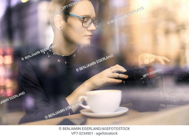 woman searching in handbag while sitting in coffee shop behind glass window, Munich, Germany