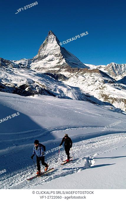Two skiers by the Station of Gornergrat with the Matterhorn summit in the background, Canton of Valais, Switzerland Europe