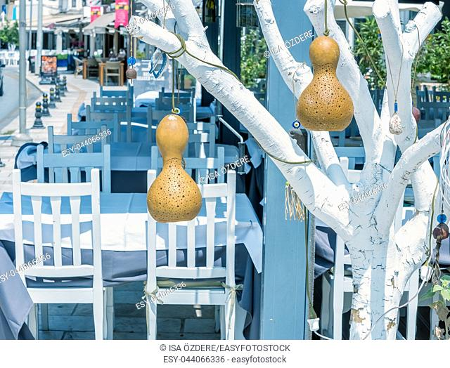 View of Bodrum streets,restaurant table and chairs with decorative calabash hanging on tree,Turkey. 23 August 2017