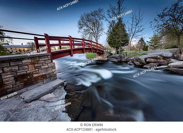 Red foot bridge over the Tay River in Stewart Park in Perth, Ontario