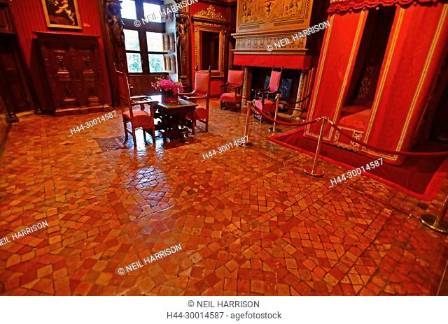 The royal apartment in a french chateau with red furnishings and red waxed terracotta tiles