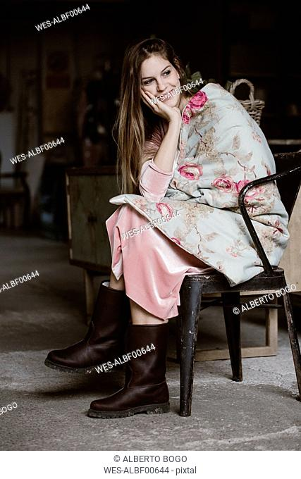 Portrait of smiling young woman sitting in a loft wrapped in blanket with floral design