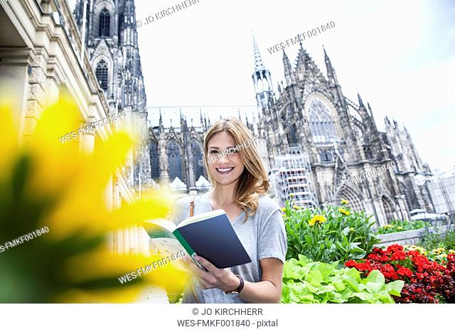 Germany, Cologne, portrait of young woman with book in front of Cologne Cathedral
