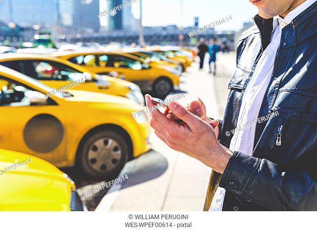 Russia, Moscow, businessman using cell phone in the city, partail view