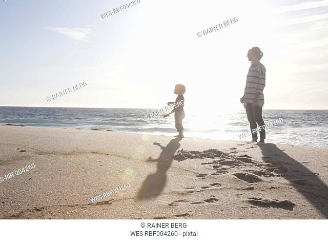 Mother standing with her little son on the beach