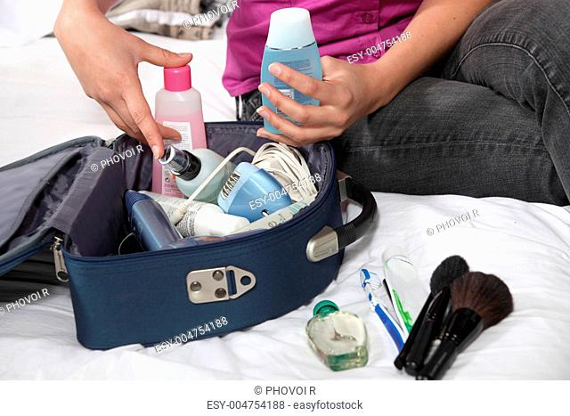 woman looking for something in her beauty bag
