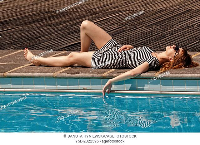 relaxed young woman in stripped dress laying at the poolside, Geneva, Switzerland