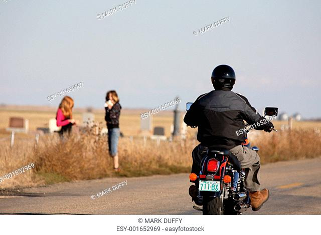 Motorcyclists passing two girls along Saskatchewan road