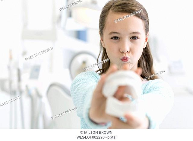Girl at the dentist holding tooth model
