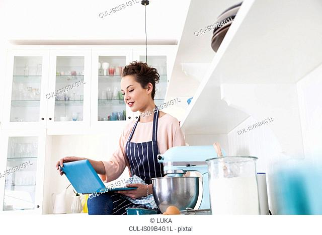 Young female baker sitting on kitchen counter looking at laptop