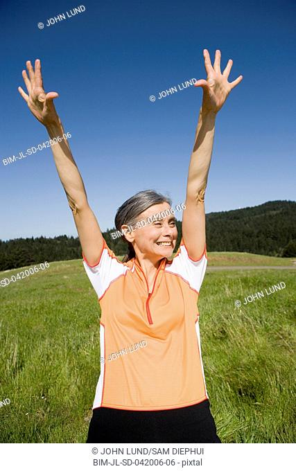 Senior woman in athletic gear with arms raised