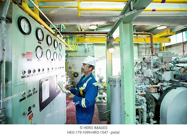 Male worker checking gauges in gas plant