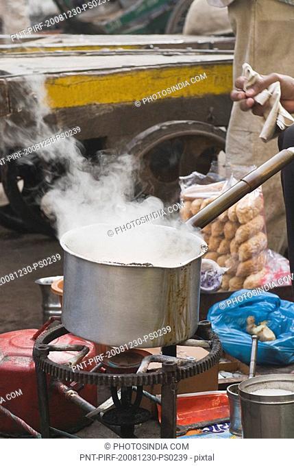 Man making tea in a market, Delhi, India
