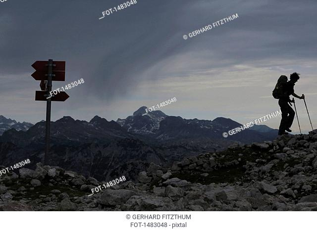 Woman hiking on rocks at mountain against cloudy sky
