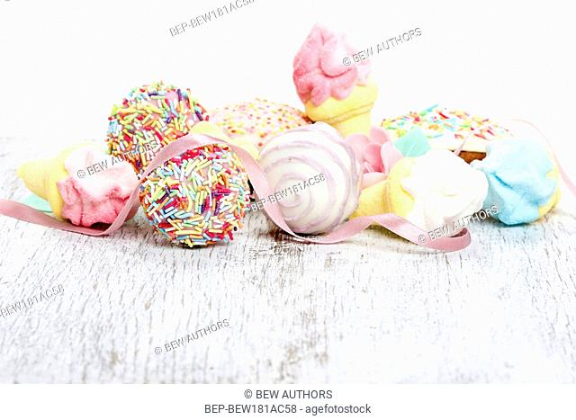 Confectionery on white wooden table, white background. Great diversity of sweets. Pastel colors