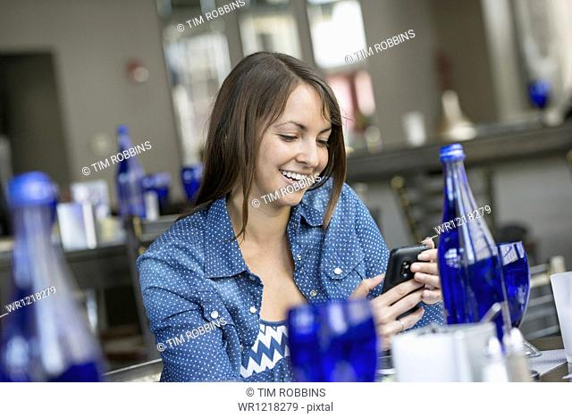 A woman seated in a cafe using a smart phone