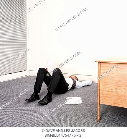 Mixed race businessman laying on floor of office