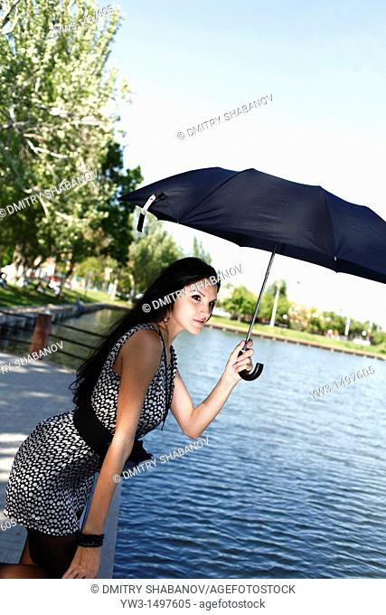 25 year old woman outdoors with umbrella near pond