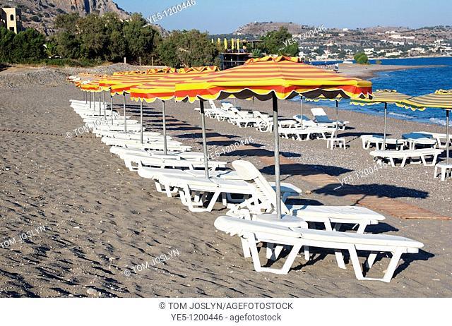 Deck chairs and parasols on sandy beach, Lothiarika , near Lardos , Rhodes , Dodecanese Islands , Greece